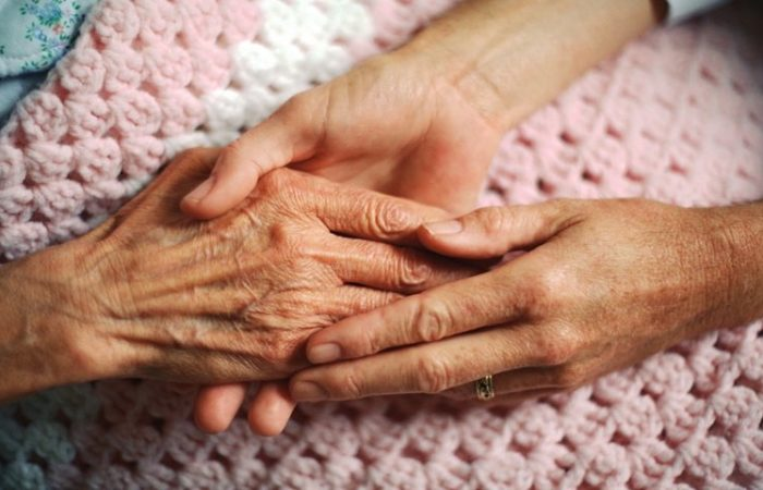A Love One Holds The Hand Of An Elderly Woman.