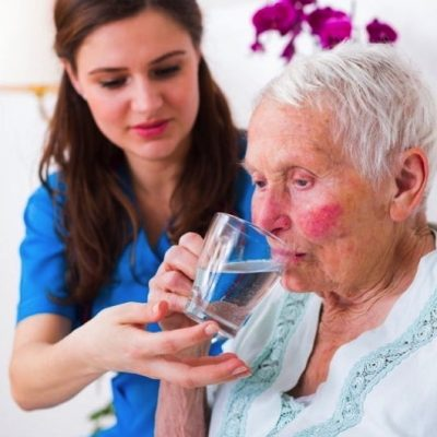 Elder Woman Getting Help Drinking Water From Younger Woman